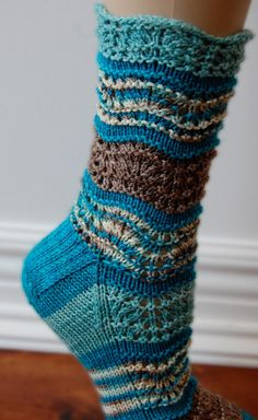 Designed by Julie Rousculp   I was inspired to design these socks after seeing (and lusting after) the incredibly fun Kells mini-skein sets. I wanted to create a sock pattern that would highlight the coordination and beauty of the skeins.  A repeating feather and fan lace pattern undulates up the leg of the sock. It is incredibly easy to memorize and that it allows these socks to simply fly off of your needles for nearly instant gratification!