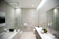 Élégante salle de bain avec murs en travertin.