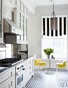 A bright Manhattan kitchen features Kartell chairs and a striped shade by Ralph Lauren Home.