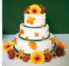 The couple cut into a three-tiered chocolate wedding cake decorated with warm autumn-colored leaves.