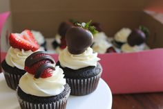 A dark chocolate cake with vanilla buttercream and a chocolate strawberry.  DoubleTroubleDesserts@gmail.com