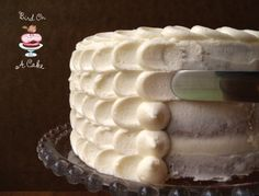 How to Frost a Cake: 1. Cover your cake with a crumb coat (very thin layer of frosting). 2. Prepare a decorating bag with a large round tip (Wilton #12). 3. Pipe a vertical line of dots on the side of your cake. 4. Use a small spatula to press down on each dot, dragging to the right. 5. Make another line of dots, just to the right of your petals. Repeat. @Patricia Smith Klomp