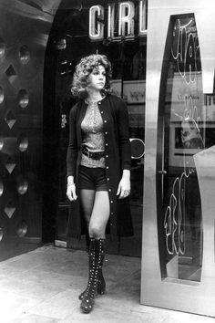 London, 1971 street style girl in hot pants shorts lace up knee boots shirt belt sweater hair 70s era mod rocker looks