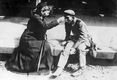 A nurse from the French Red Cross helps a beggar, Germany, 1914-1918