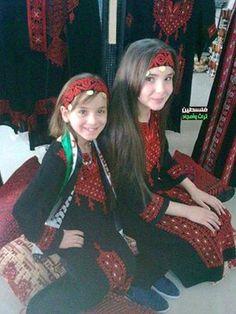 "Two Palestinian girls , wearing the traditional Palestinian ""Thoab"" / dress ."