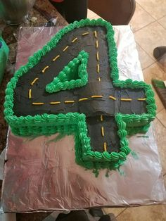 Car cake. Road cake. Car track cake. Number 4 cake. I made this for my nephew and my sister added cars and little racing flags.