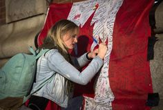 A woman writes a message on a Canadian flag at a makeshift memorial in honor of Cpl. Nathan Cirillo, outside the Lieutenant-Colonel John Weir Foote Armoury October 24, 2014.  REUTERS-Mark Blinch