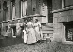 Drie dienstboden met lange rokken en schorten staan bij elkaar op de stoep...