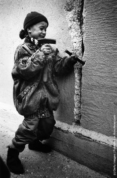 Berlin Wall. A little girl chisels away at the Berlin Wall from the east side on New Year's Eve, 31st December 1989. (Photo by Steve Eason/Hulton Archive/Getty Images)