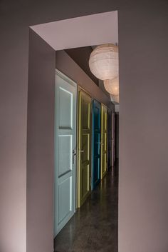 Corridor long, narrow and lined with doors? Effective tip: paint the doors with different col Door Paint Colors, Wall Colors, House Colors, Hallway Decorating, Interior Decorating, Hotel Corridor, Colour Architecture, Inside Doors, The Doors
