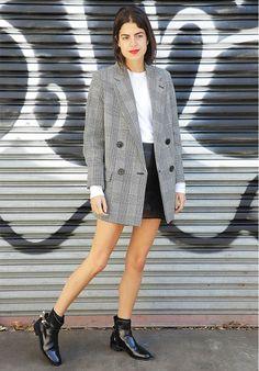 Leandra Medine of the Man Repeller wears a white t-shirt, mini skirt, plaid blazer, and black ankle boots