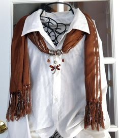 Elegant scarf in brown with silver threads. The pendant for this item is a large dragonfly with matching drops on each side. Scarf is 62 inches long with fringe on the ends.