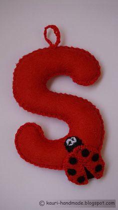 """FILCOWA LITERKA """"S"""" w kolorze czerwonym z naszytą filcową aplikacją w kształcie biedronki."""