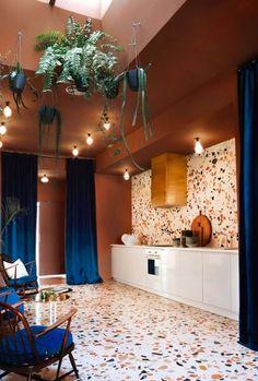 Piso y pared de terrazzo. Esta estancia es ideal para los amantes del color. Plantas colgantes son perfectas para decorar con elementos vivos. Además las paredes rojas con la silla azul y las cortinas largas azules dan el toque ideal. #Plantascolgantes