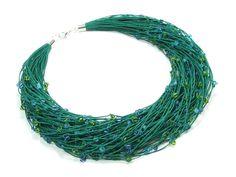 Naszyjnik wykonany ręcznie na bazie przędzy lnianej, w którą wpleciono koraliki szklane w odcieniach niebieskiej i zielonej barwy. Długość naszyjnika około 49cm. Wykończenia posrebrzane.