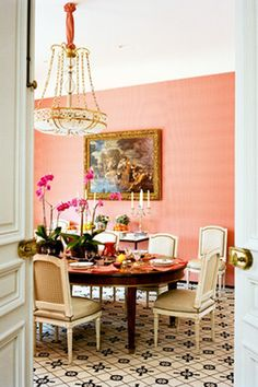 I really like the peachy/pink salmon wall for a dining room. And the fresh flowers help give the space a sense of life.