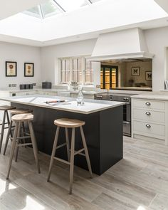 This kitchen island is painted in a darker colour to the rest of the kitchen and helps it to become a focal point.
