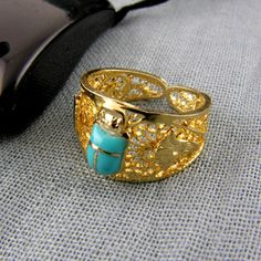 unique Egyptian ring ,the ring is 18k handmade gold and feature a turquoise scarab at the front and surrounded by lotus flowers, the ring  measure about 5.5 grams