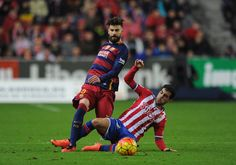 Gerard Pique of FC Barcelona is tackled by Carlos Castro of Sporting Gijon during the La Liga match between Sporting Gijon and FC Barcelona at Estadio El Molinon on February 17, 2016 in Gijon