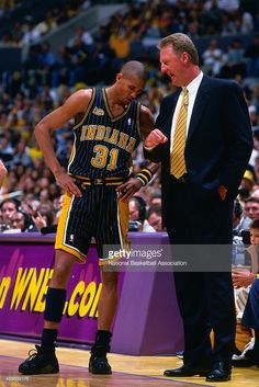 Head coach Larry Bird of the Indiana Pacers speaks with Reggie Miller #31 against the Los Angeles Lakers during a game in the 2000 NBA Finals at STAPLES Center in Los Angeles, California.