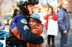 """This photo of Devonte Hart, a 12-year old boy, hugging a police officer at a Ferguson protest in Portland, Oregon, on Tuesday has gone viral and been dubbed """" the hug shared around the world. """""""