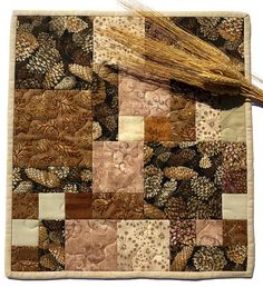 Quilted Fall Table Topper with Pinecones, Brown and Beige Autumn Table Cloth, Candle Mat, Quilted Centerpiece, Quiltsy Handmade  This quilted Fall or Autumn Table Topper is made with a beautiful fabric featuring pinecones. Ive highlighted the pinecone fabric with other fabrics in various shades of browns and beiges. It measures approximately 13.75 x l5.25 inches. All my products are made with quality quilting cotton fabric. The table topper is machine stitched and machine quilted using the…