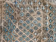 When U.S. military airplanes need to be repaired or are just too old to fly, many of them end up in the Aerospace Maintenance and Regeneration Center, or AMARC, in Tucson, Arizona. Some of these planes are restored to operational status while others are broken down for parts. Seen from above, the planes make beautiful patterns in blue and white against the earthy brown backdrop.