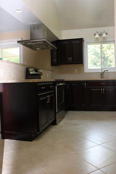 light tile floor, dark espresso cabinets, and golden countertop