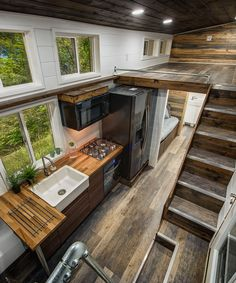 Grizzly von Backcountry Tiny Homes In the kitchen you'll find a gas cooktop with overhead microwave, oven, full size side-by-side refrigerator, farmhouse sink, and butcher block counter. The counter has an extension that serves as an eating area. Tyni House, Tiny House Loft, Modern Tiny House, Tiny House Living, Tiny House Plans, Tiny House Design, Tiny House On Wheels, Tiny House Kitchens, Tiny House Stairs