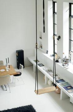 Balançoire suspendue dans appartement blanc et bois