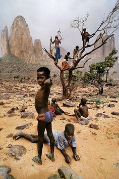 """Steve McCurry. Información desde el primer plano hasta el fondo. Con sensación de profundidad mediante la comparación inconsciente de las estaturas. La mirada del crío en primer plano """"mete"""" al espectador dentro del entorno, al mirarlo directamente. Los críos en los árboles apenas se superponen con las rocas (forman así un marco para ellos)."""