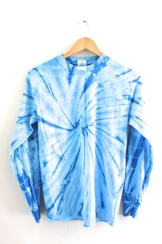 Medium and light blue tie-dyed long sleeve, 100% cotton t-shirt. Please note: Each tie-dyed tee is hand dyed and slightly unique. Washing instructions: Machine wash inside out in very cold water, dry