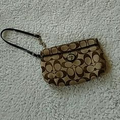 ??Coach Wristlet ??Coach Wristlet...tan and brown large wristlet with small outer pocket...never really used...in excellent condition Coach Bags Clutches & Wristlets