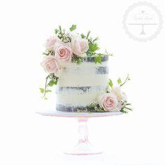 Semi-naked wedding cake with fresh blooms.