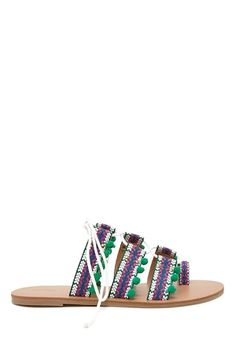 A pair of sandals featuring an embroidered tribal print, a toe ring and strappy design, lace-up top, pom pom trim, and burnished studs.