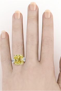 This eye-catching ring showcases an extraordinary 16.57-carat fancy yellow diamond. The rare gem is certified by the GIA as natural fancy yellow and Internally Flawless. To find an untreated fancy colored diamond of this size and clarity is spectacular. The emerald-cut stone is flanked by two diamonds in its platinum and 18k gold setting ~ Engagement Ring, High Jewelry, Rare gemstones ~ M.S. Rau Antiques