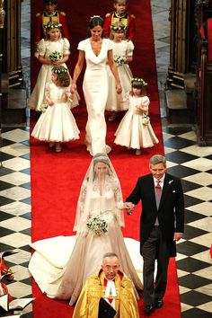 4/29/11: Kate Middleton going down the aisle with her father at her wedding to Prince William. Kate's sister follows her with several young attendants.