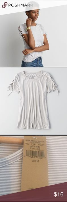 "American Eagle lace up T shirt NWT This shirt is SO cute. It's gray and white small stripes that are kind of hard to see in the pics. The first two photos are from AE's site. The short sleeves lace up. It's one of the ""soft and sexy"" tees and it really is so so soft. So cute and on trend! Brand new with the tags American Eagle Outfitters Tops Tees - Short Sleeve"