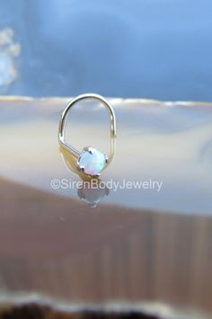 Featuring a creamy 2.5mm white opal, this solid 14k gold nose ring screw is a thing of beauty. Classy and petite, this 20g nose piercing ring is a nice complimentary piece to any outfit. Ideal for everyday wear. $49.99+S&H SirenBodyJewelry Nose Rings Nose Screws Nose Piercings Gold Nose Ring Gold Nose Stud Nostril Piercing Jewelry Body Piercing Jewelry
