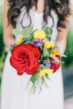 Vibrant & Petite Bridal Bouquet Showcasing: Big Red Garden Roses, Blue Hydrangea, Yellow Freesia, Purple Sweet Pea, Lavender, Green Seeded Eucalyptus & Additional Greenery/Foliage