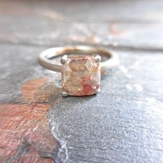 The roughness of this raw diamond ring is balanced by the stone's grayed blush hue, which gives the piece a soft edge.