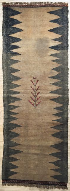 SOUFREH, 'LIVETS TRÆ' Denne Soufreh er en lys brun kelim (fladvævet) med et sort zigzagmotiv på hver langside og med broderede striber i hver ende. Midt på tæppet er symbolet på Livets Træ broderet. Tæppet er vævet af kurdiske stammer i Iran af ren kameluld. Vintage: 60-80 år Størrelse: 186*65 cm