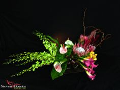 Tropical floral arrangement of woven palm fronds, Orchids, Calla's, Anthuriums and King Protea.  Designed by Steven Bowles Creative, Naples, FL www.stevenbowlescreative.com
