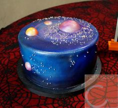 Grooms cake is 10 inch carrot cake with cream cheese buttercream, fondant with chocolate planets and air brushed to resemble a far off galaxy.