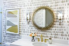 Gold and gray bathroom features walls clad in gray print wallpaper, Byzantium Wallcovering Collection Queen of Spain Wallpaper, lined with a gold sunburst mirror illuminated by mirrored sconces over a white quartz top vanity fitted with an oval sink and gold faucet kit.