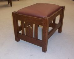 New Mission Oak Footstool with an Arts & Crafts stylized cut out design in the side slats.  Made of quarter-sawn white oak. The cushion is leather covered.  Other styles available, including an arrow cut out design or side slats with no cut outs.    Dimensions: 19″ wide X 15″ deep X 13 1/2″ height    $325