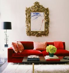 Mirror, mirror on the wall, which is the most ornate of them all? We think this intricate golden mirror that is beautifully hung over a red living room couch is the one!