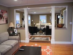 neutral family room with pops of orange opens up into more formal living room