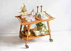 60s Vintage tea cart I love the sleek Scandi lines of this delicately designed piece. Very minimal with twist and at the same time very elegant and timeless. The frame is made of solid wood and the shelves are veneered wood. The wheels are made of brass and rubber. The wheels have been oiled and are working perfectly. Thanks to the handles you can pull your bar cart to where you need it.  Use it traditionally as a mini bar, or for your favorite books, your knitting, your favorite bags, as a…