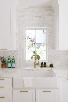A sleek kitchen with a small dish window, gold hardware, white cabinents, and marble backsplash Source by mydomaine Gold Kitchen, New Kitchen, Kitchen Decor, Kitchen White, Kitchen Sink, Kitchen Ideas, Home Design, Interior Design Kitchen, Design Design